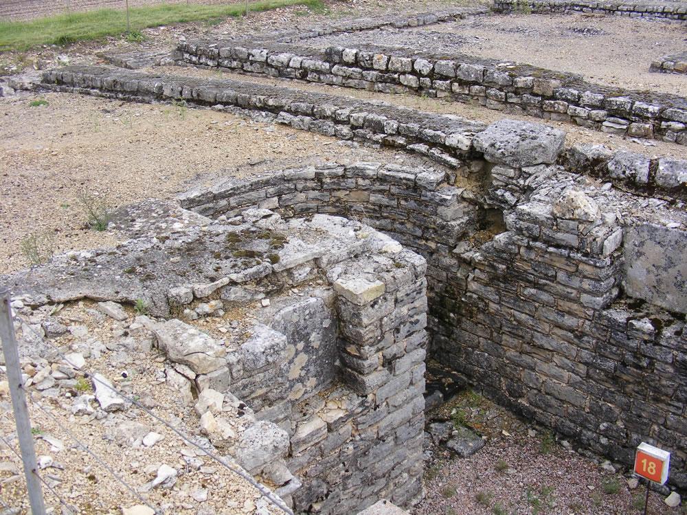 Blick auf eine Ausgrabung in Alesia, gut erhaltene Wohnwände mit teilweise sehr guten erhaltenen Stufen in die Keller der Häuser