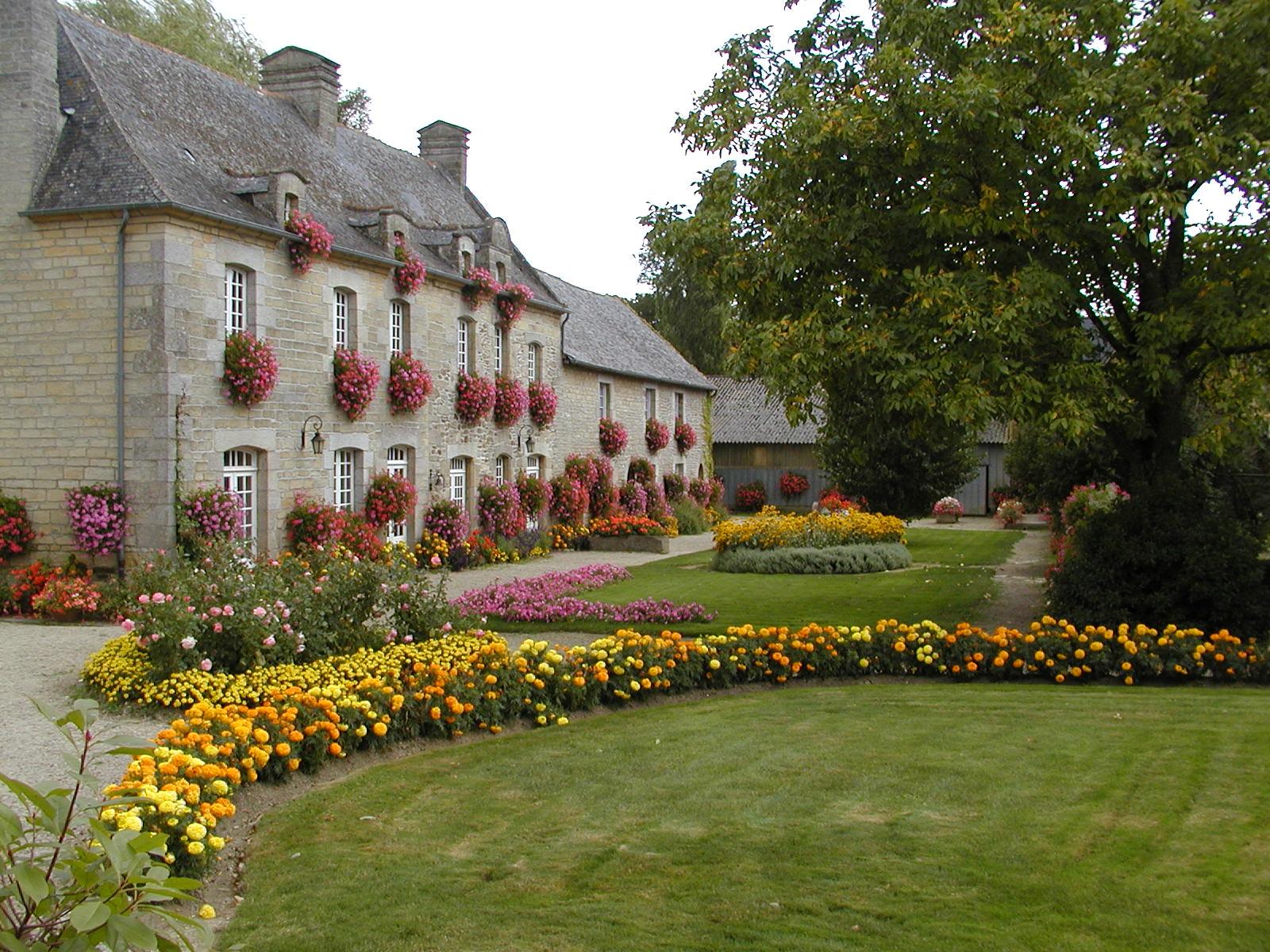 Ein schöner Bauernhof in St. Juvat, Cotes-d'Armor im Nordwesten von Frankreich mit einer prachtvollen Parkanlage vor dem Hof.