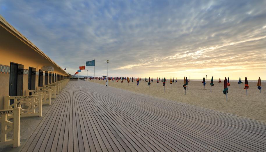 Der Strand von Deauville am Abend mit einem romantischen Sonnenuntergang. Der Luxusurlaubsort in Deauville bietet einen Kilometerlanger Sandstrand.