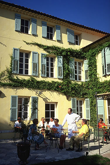 Ein idyllisch gelegenes Restaurant im Innenhof in Frankreich. Der Garçon nimmt die Bestellungen der Kunden auf