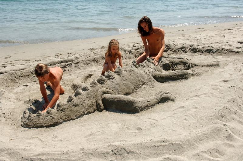 Sandburgenbauen beim FKK Urlaub auf Korsika. Urlaub mit Familien und Kindern auf einen der vielen Camping und FKK-Zentren Korsikas.