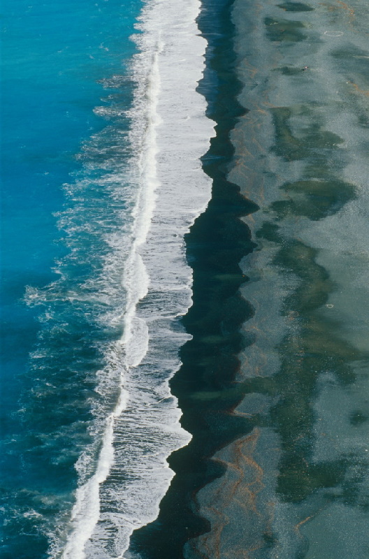 Die Wellen brechen am Strand. Beeindruckende Luftaufnahme vom Cap Corse: Dunkler Strand von Nonza auf Korsika.