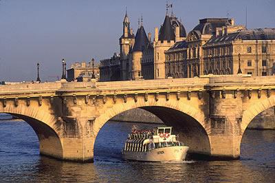 Blick vom Quai du Louvre auf den Pont Neuf, die älteste noch erhaltene Brücke über die Seine in Paris. Unter der Brücke eine Bootstour.