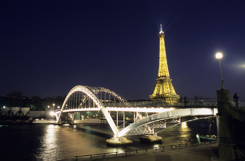 Beleuchteter Eiffelturm, davor die Passerelle Debilly über die Seine. Der als Höhepunkt der Pariser Weltausstellung von 1889 errichtete Eiffelturm.