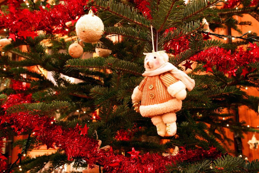 Ein Weihnachtsbaum mit roten Girlanden und goldenen Kugeln.